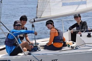 ヨット上の4人がこちらに微笑む